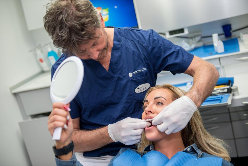 Carina Dahl sin tannlege hos Oris Dental setter på Invisalign, som er en usynlig tannregulering for voksne. Foran seg holder hun et speil for å se hvor lite synlig regulering er.