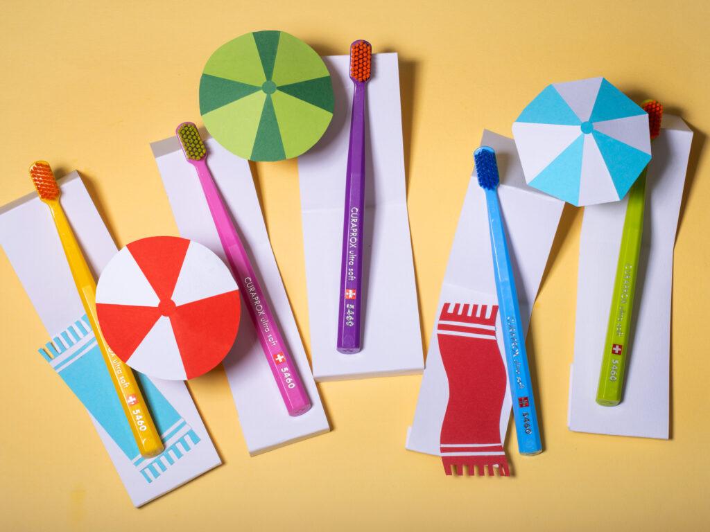 Curaprox tannbørster lagt på biter av papir slik at det ser ut som de ligger på en strand.