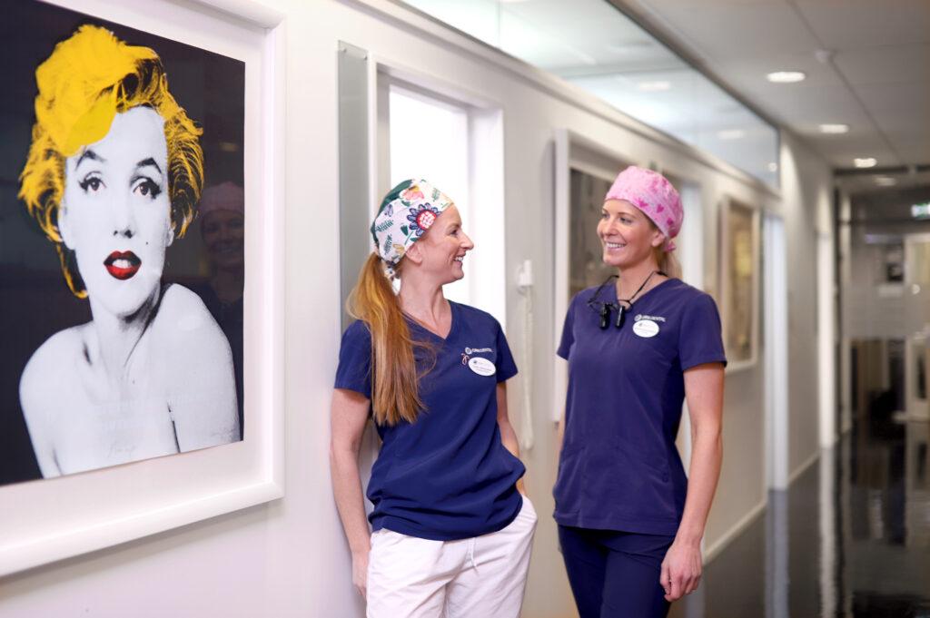 To kvinnelige tannleger ved Oris Dental Lysaker smiler til hverandre i korridoren uten for rommene for tannbehandling.
