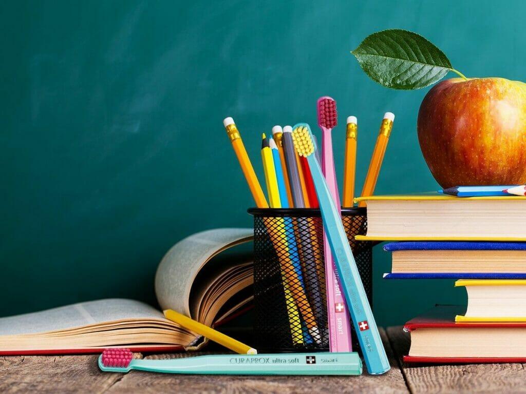 Tannbørster på skrivebord sammen med blyanter. Vår tannlege påviser at tannbørsten er like viktig som blyanten under studietiden.