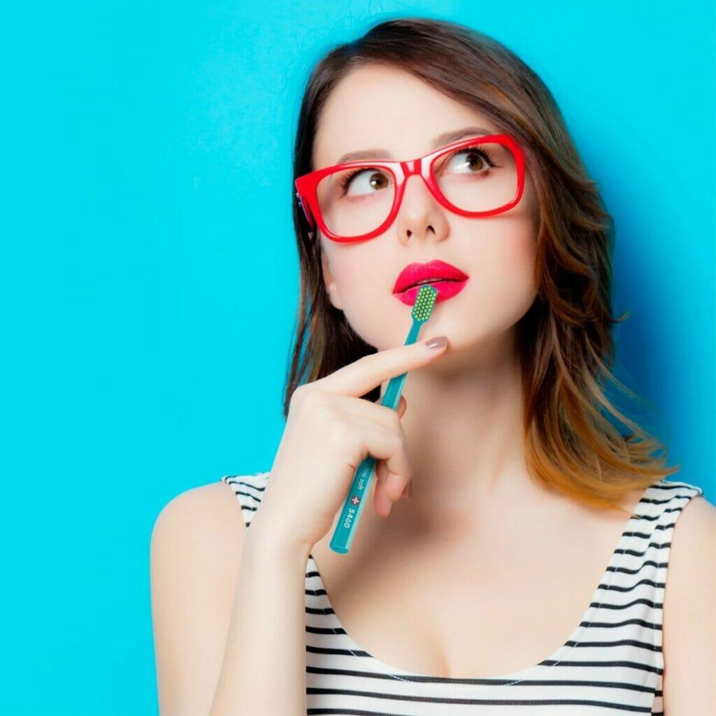 Student med tannbørste i munnen, som vurderer om hun skal besøke en tannlege hos Oris Dental.