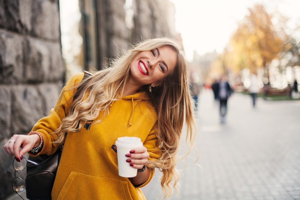 Glad jente smiler bredt etter å nettopp ha fått behandling hos tannlege for student ved Oris Dental i Trondheim