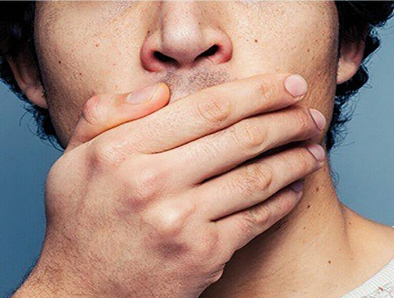 Mann holder hånd foran munnen for å skjule smilet, ettersom han mangler tenner.
