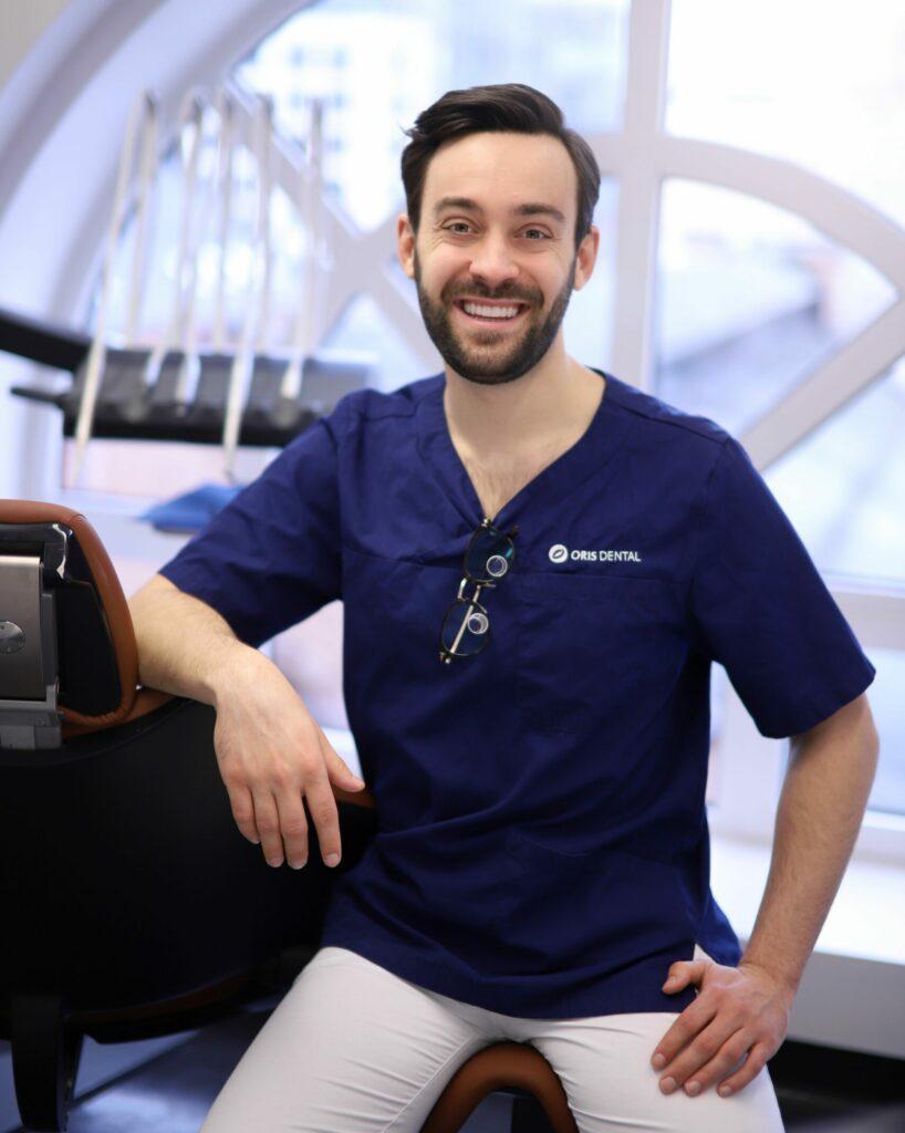 Tannlege Sebastian sitter ved tannlegestolen på behandlerrommet ved Oris Dental Aker Brygge, hvor han tilbyr gratis konsultasjon for behandling med Invisalign, usynlig tannregulering.