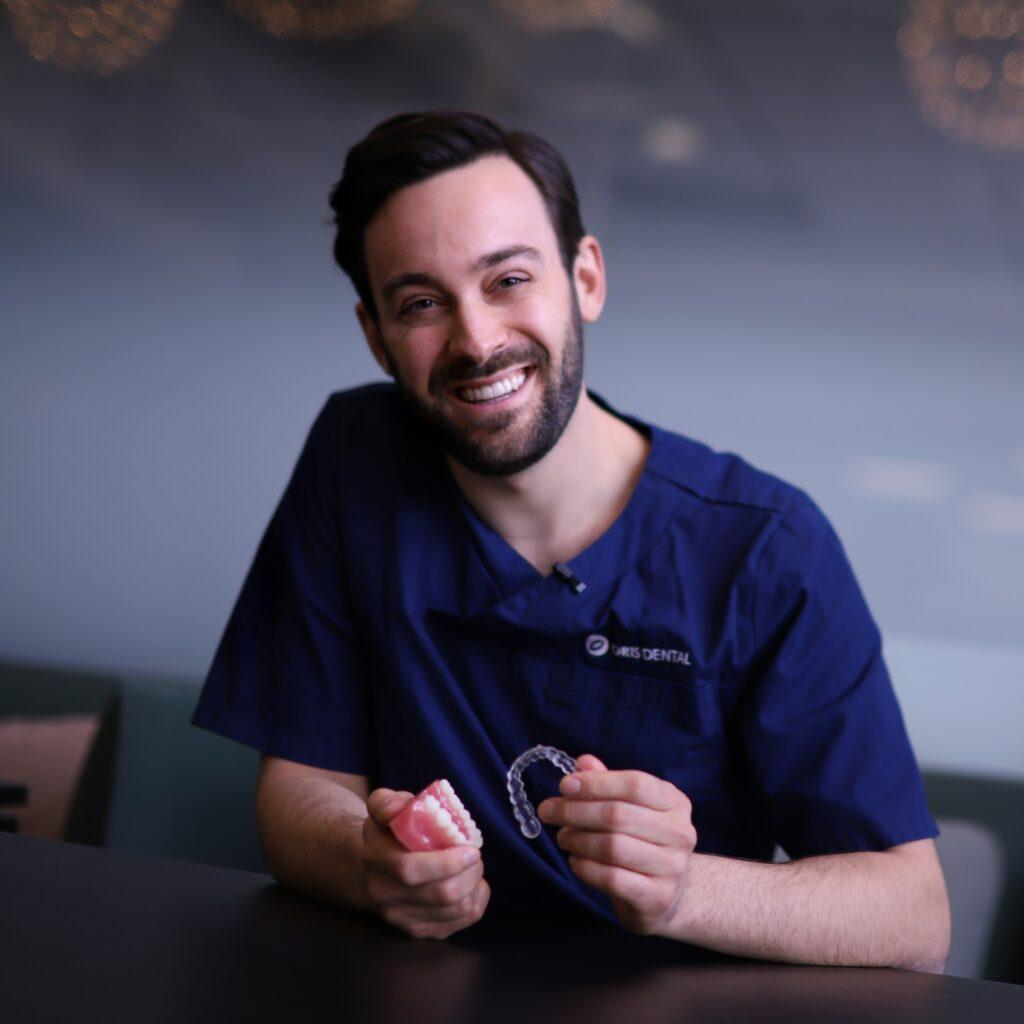 Tannlege ved Oris Dental viser frem en usynlig tannregulering.