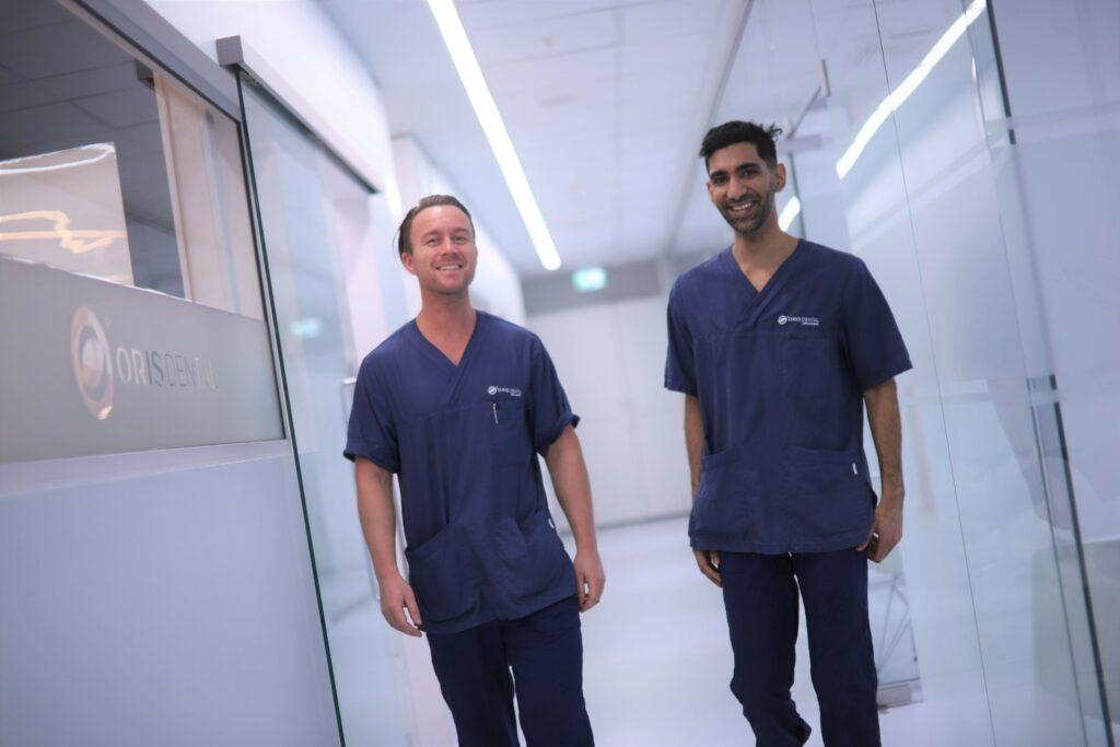 De dyktige tannlegene Vineet og Kenneth spaserer nedover gangen utenfor behandlingsrommene ved Oris Dental Orkanger.